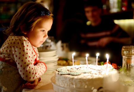 pasteles de cumplea�os: Ni�a soplando las velas en su cumplea�os (enfoque superficial)