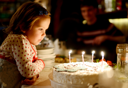 Little girl blowing out candles in her birthday (shallow focus) photo