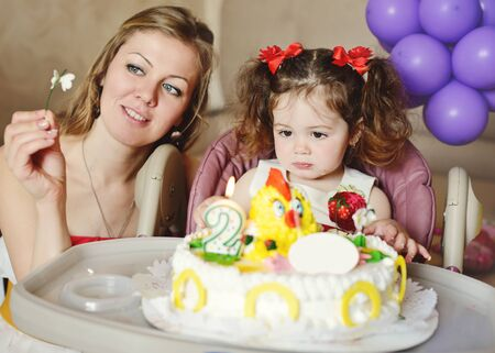 happy people white background: toddler girl anf her mother sitting with birthday cake