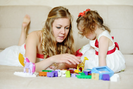 Mother with a little daughter playing with blocks at home