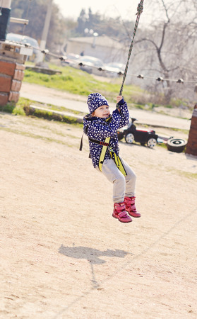 rappelling: aсtive toddler girl  in the rope park