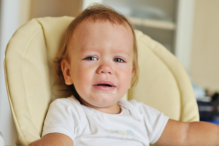 tearful: little baby is crying and sitting on thr chair Stock Photo