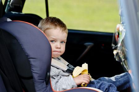 the seat: niño pequeño sentado en el asiento del coche y comer un plátano