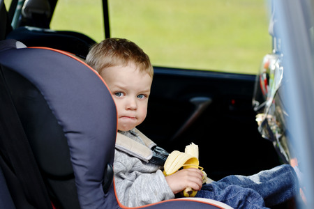 toddler boy sitting in the car seat and eating a banana