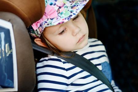 bebe enfermo: niña cansada en el asiento del coche Foto de archivo