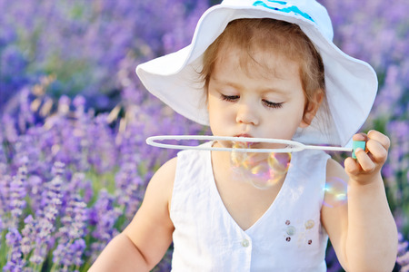 toddler girl in lavender field with soap bubbles