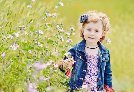 pretty toddler girl in spring near the flowers photo