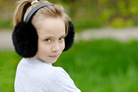 earmuff: portrait of cute blonde girl outdoors in spring time