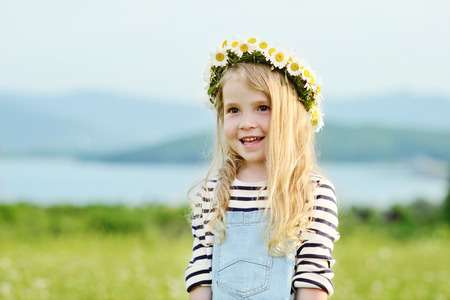 happy girl in field with a garland on the head