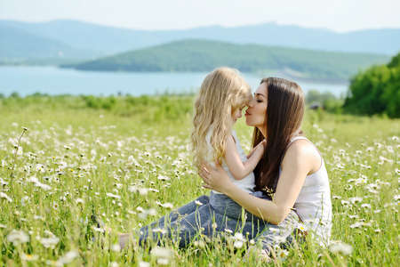 mother hugging with toddler girl in daisy field Stock Photo
