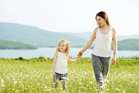 mother and daughter in field of daisies Stock Photo