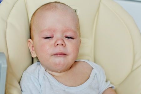 tearful: little baby is crying and sitting in the chair