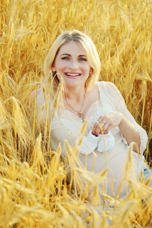 bootee: pregnant woman laying in wheat field with bootee on tummy
