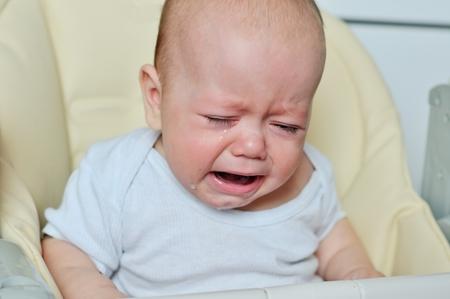 ojos llorando: pequeño bebé está llorando y sentado en la silla