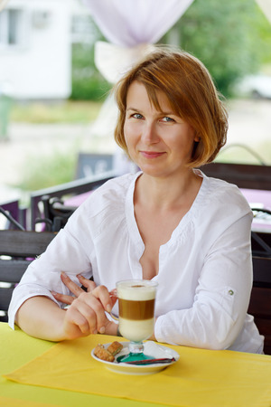 ordinary woman: ordinary woman sitting in cafe with cup of coffee Stock Photo