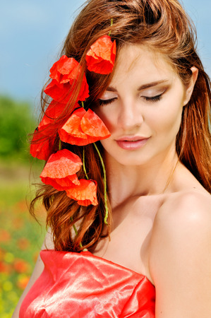 beatiful girl with poppies in red hair photo