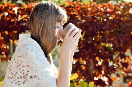 girl with mug of hot drink in sunny fall day photo