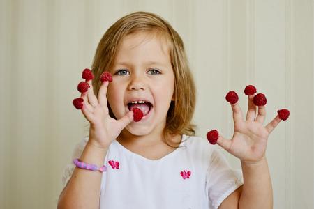 raspberry dress: happy girl with raspberry on her fingers