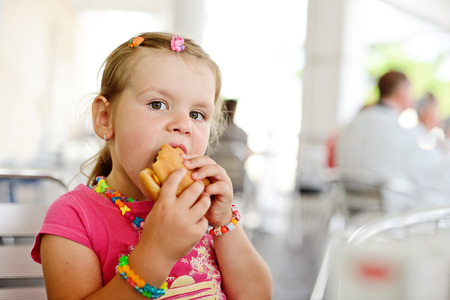 little girl eating a hamburger in outdoor cafe photo