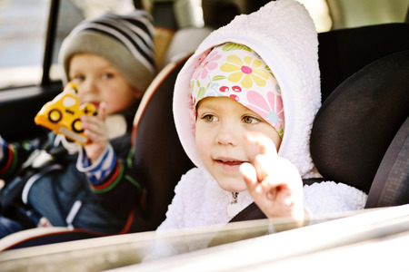 restraints: girl and her brother  traveling in baby car seats
