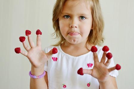 raspberry dress: little girl with raspberry on her fingers