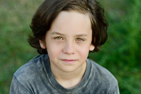 capelli lunghi: felice ragazzo preteen sorridente con i capelli lunghi