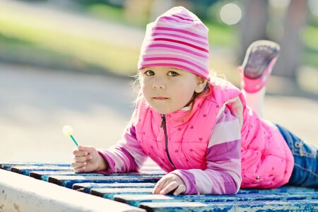sugarplum: sweet toddler girl in the park laying on the bench