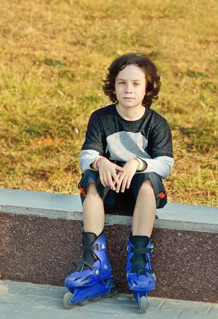 ni�o en patines: boy vistiendo patines preteen sentados al aire libre