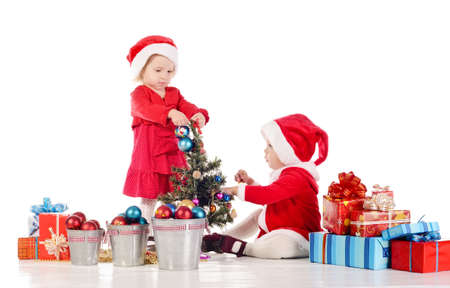 helpers: two little santa helpers decorating a tree Stock Photo