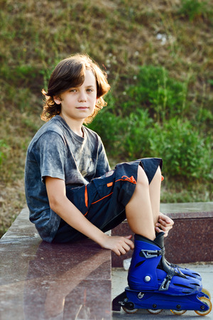 niño en patines: boy vistiendo patines preteen sentados al aire libre
