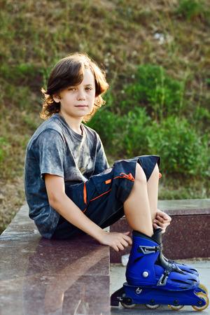 ni�o en patines: preteen boy wearing roller skates sitting outdoors