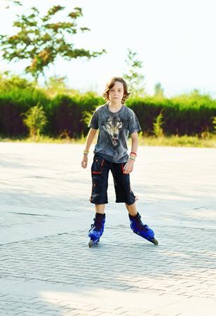 ni�o en patines: boy vistiendo patines preadolescente que juega al aire libre