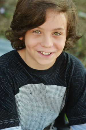 10 11 years: happy smiling preteen boy with long hair