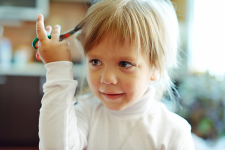 nursery school: Cute toddler girl with scissors wants to cut hair Stock Photo