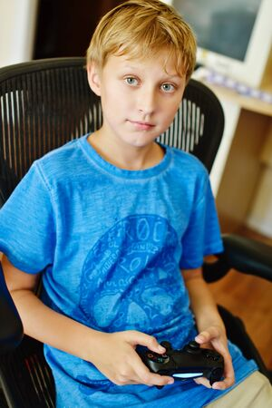 preteen: preteen boy at home with video game controller