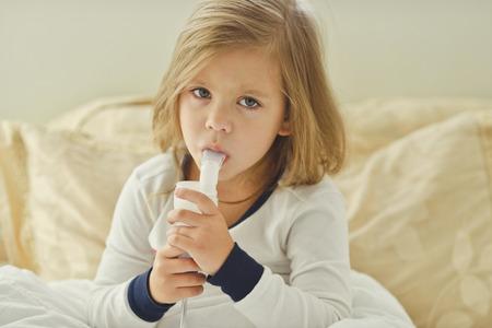 atmung: kleines Mädchen mit Husten zu Hause mit Inhalator