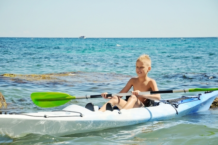 cayak: Happy preteen  boy on a kayak in sea Stock Photo