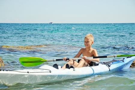 preteen boy: Happy preteen  boy on a kayak in sea Stock Photo