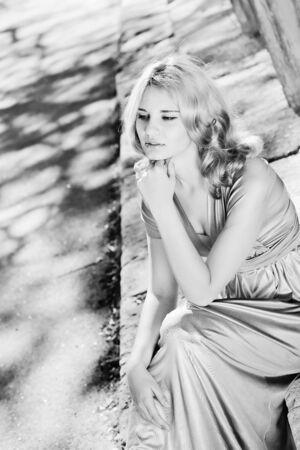 pretty lady sitting in sun light near the columns photo