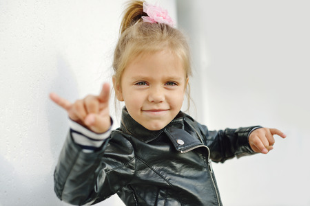 portrait: cute little girl making a rock-n-roll sign Stock Photo