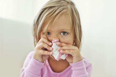 sick toddler girl with handkerchief at the home Standard-Bild