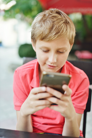 only one teenage boy: blonde boy playing phone in outdoor cafe Stock Photo