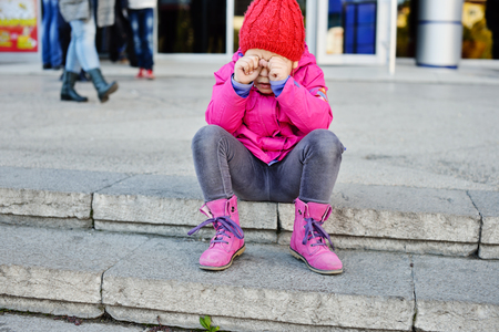 disobedient child: lost girl in the city sitting and crying Stock Photo