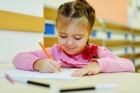 preschooler: little preschooler girl is drawing in kindergarten