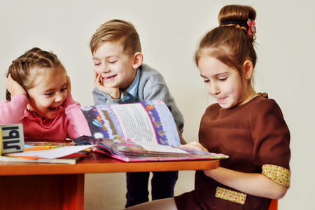 kindergarten education: children in kindergarten reading books and laughing Stock Photo