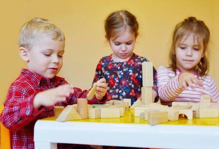 children playing wooden blocks in the kindergarten