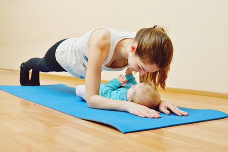 mum and daughter: young mother does physical yoga exercises together with her baby