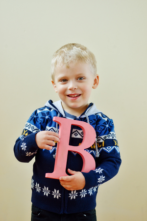 fundamentals: toddler boy is standing with letter B Stock Photo