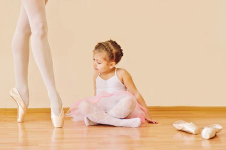 meisje op zoek op de voeten van de trainer in balletschool