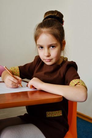 grade schooler: little preschooler girl is drawing in kindergarten